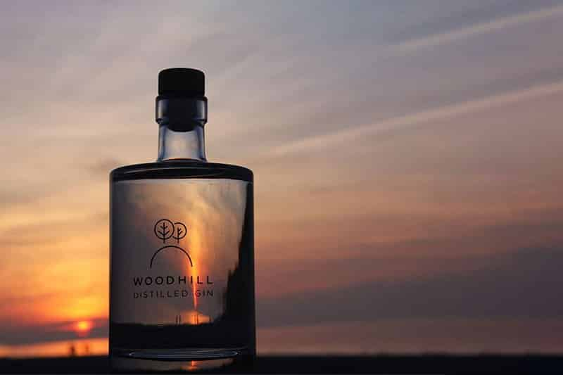 En flaske Woodill gin i solnedgang