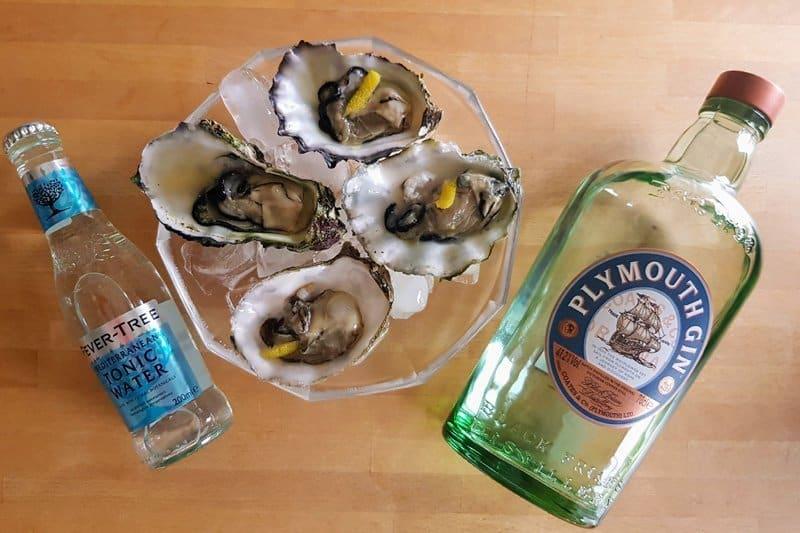 Et fat med 4 østers som er dryppet med Plymouth Gin og Feve-Tree Mediteranean Tonic Water